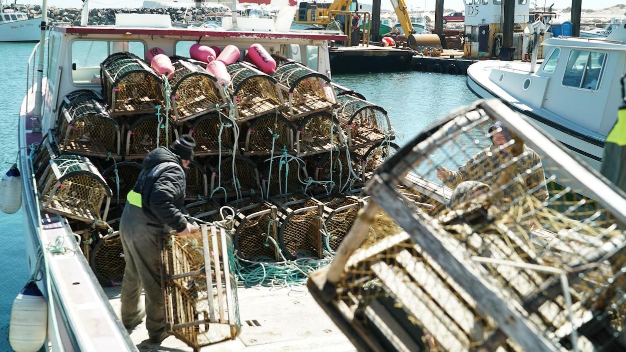 Un homme qui range des casiers à homard sur un bateau