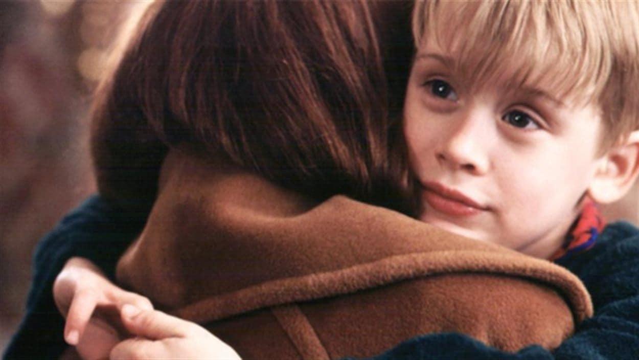 L'enfant est dans les bras d'une adulte.
