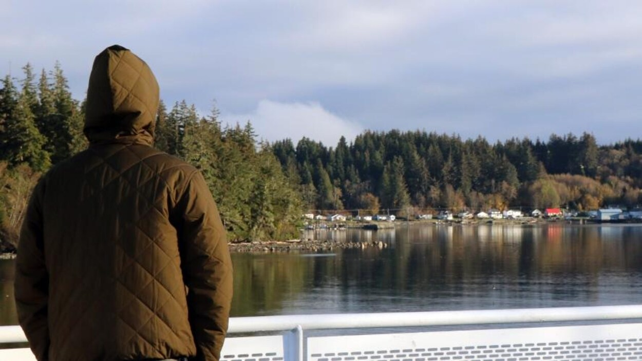 Une personne debout sur le pont d'un traversier regarde une côte où se trouvent plusieurs maisons adossées à une forêt dense.