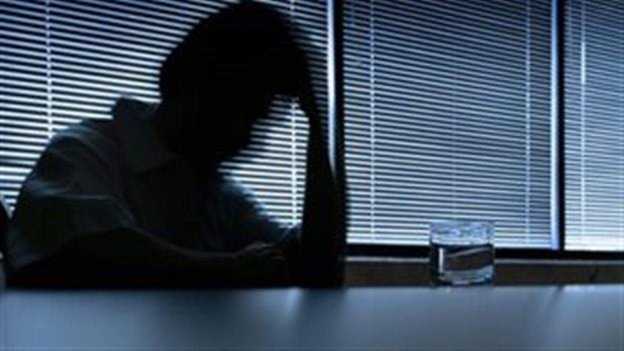 Silhouette d'un homme dépressif assis à une table devant une fenêtre.