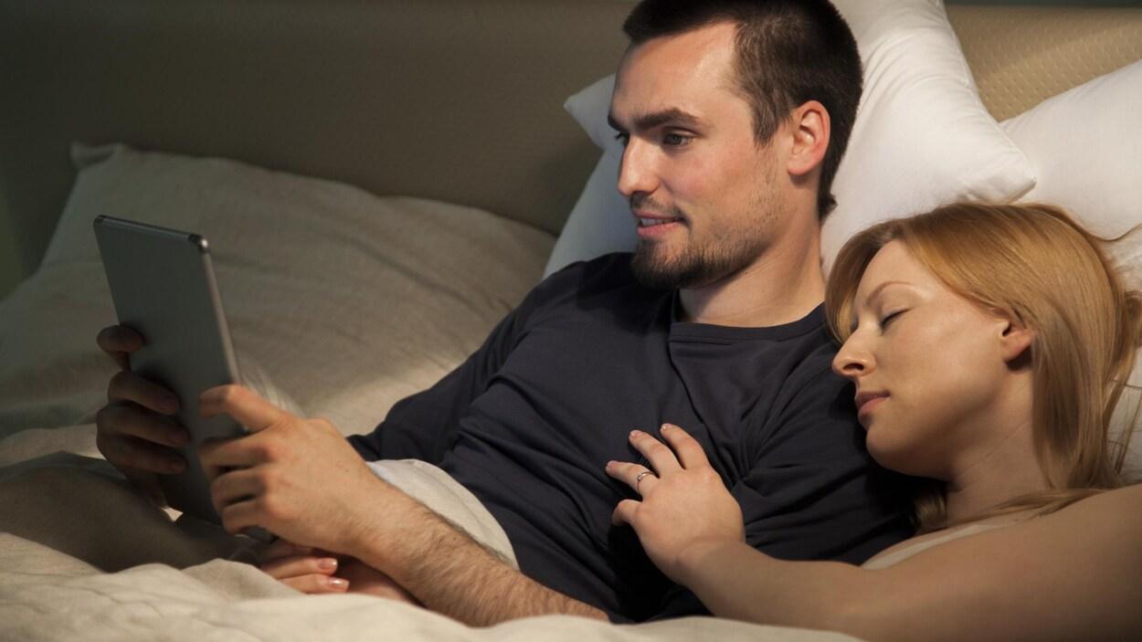 Un homme consulte sa tablette alors que sa femme dort à côté de lui.