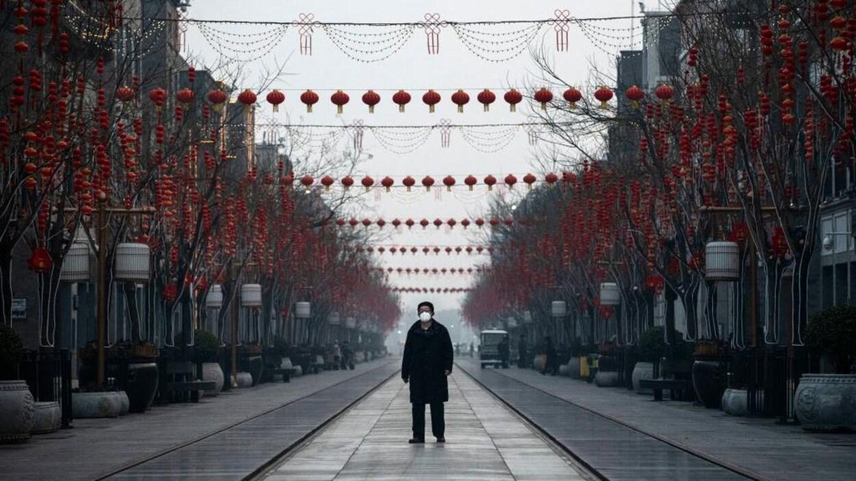 Un homme porte un masque de protection dans une rue à Pékin.