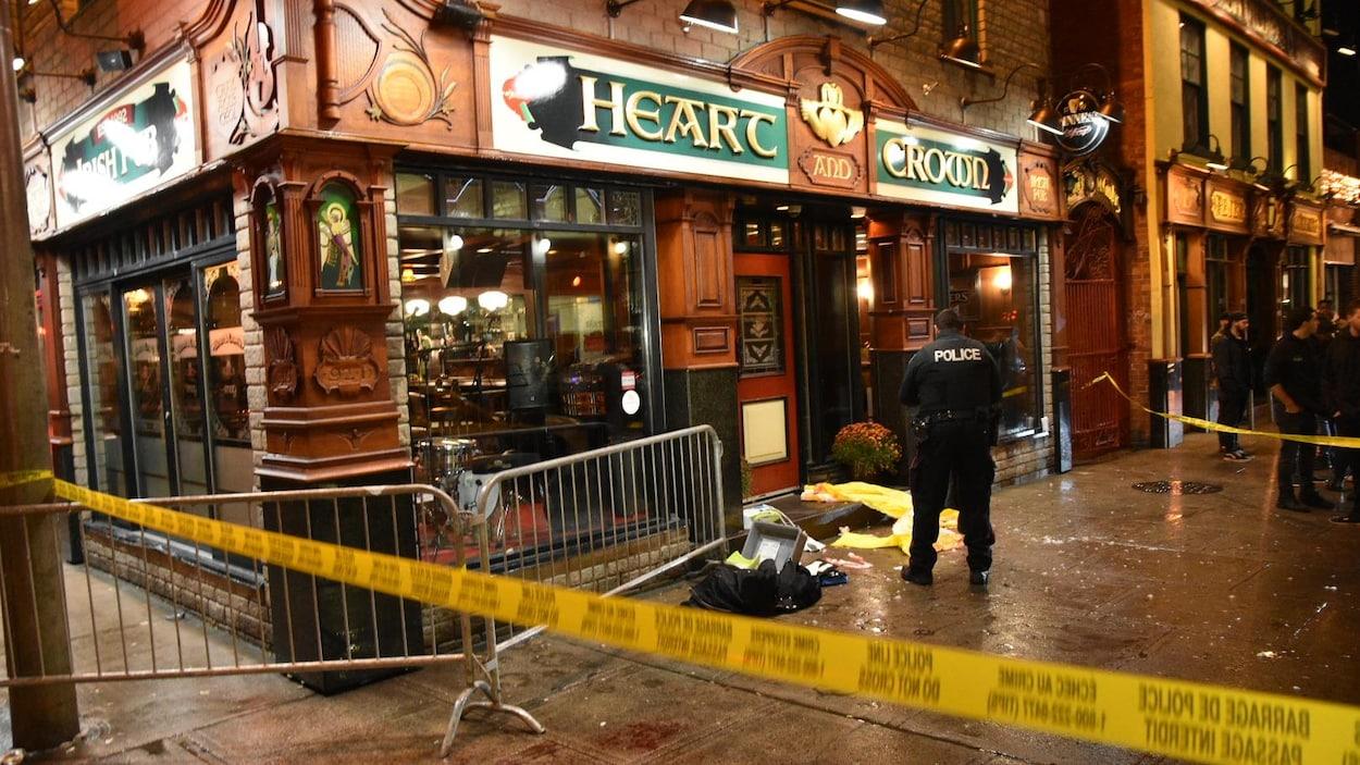 Un périmètre de sécurité autour de la porte d'un bar. Un policier se trouve à l'intérieur du périmètre.