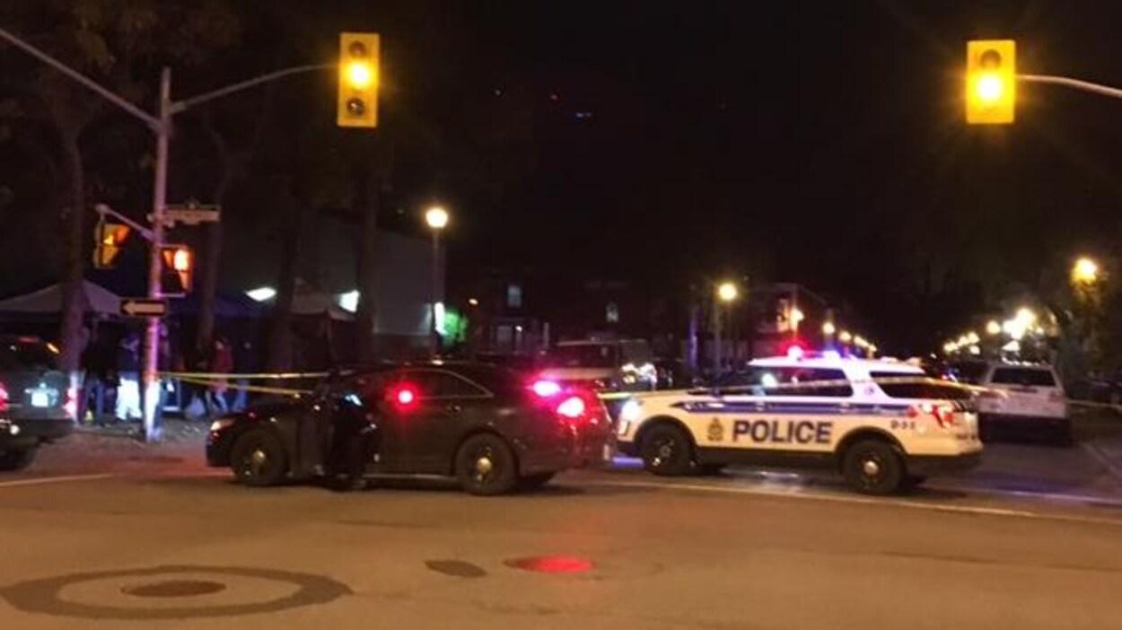 Deux véhicules du Service de police d'Ottawa à une intersection près d'un parc la nuit