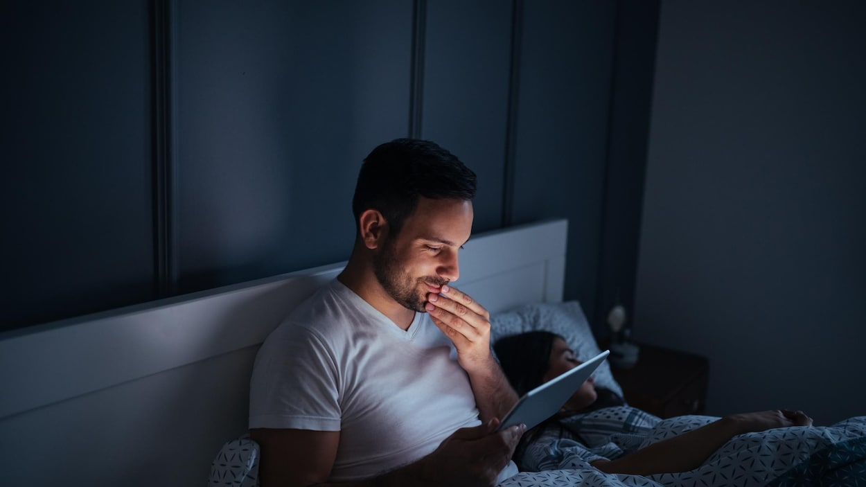 Un homme consulte sa tablette dans son lit.