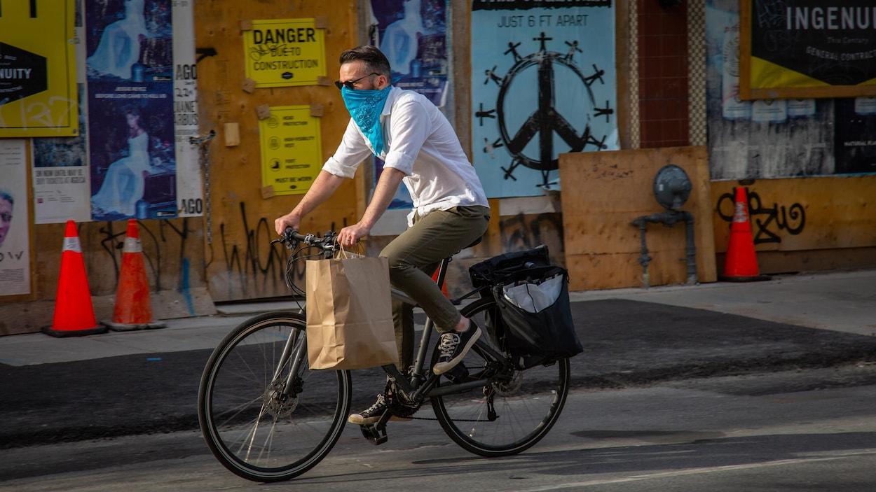 Un homme à vélo avec un bandana sur le nez.