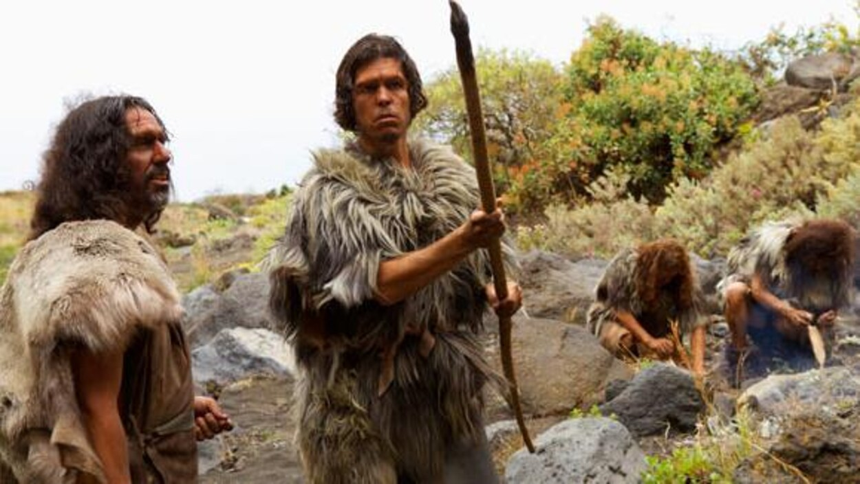 Deux hommes de Néandertal regardent une lance.