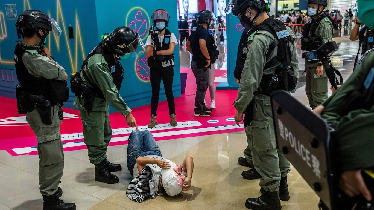 Des policiers entourent une femme qui est couchée par terre sur le dos. L'un d'entre eux pointe le doigt dans sa direction.