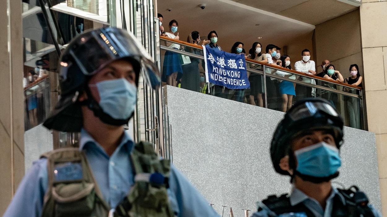 Des manifestants déploient une bannière disant « Indépendance de Hong Kong », vue entre deux agents de police.
