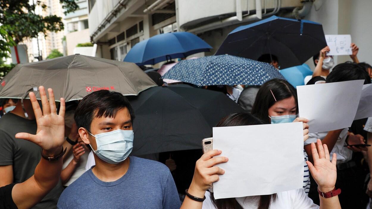 Plusieurs personnes réunies dans la rue, portant des masques, des pages blanches et des parapluies.