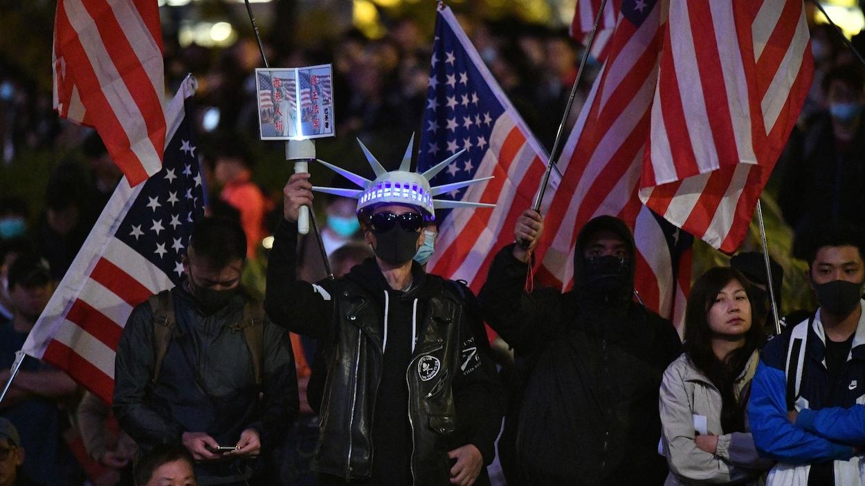 Trois hommes masqués brandissent des drapeaux américains au milieu d'une foule. L'un d'eux est déguisé en statue de la liberté.