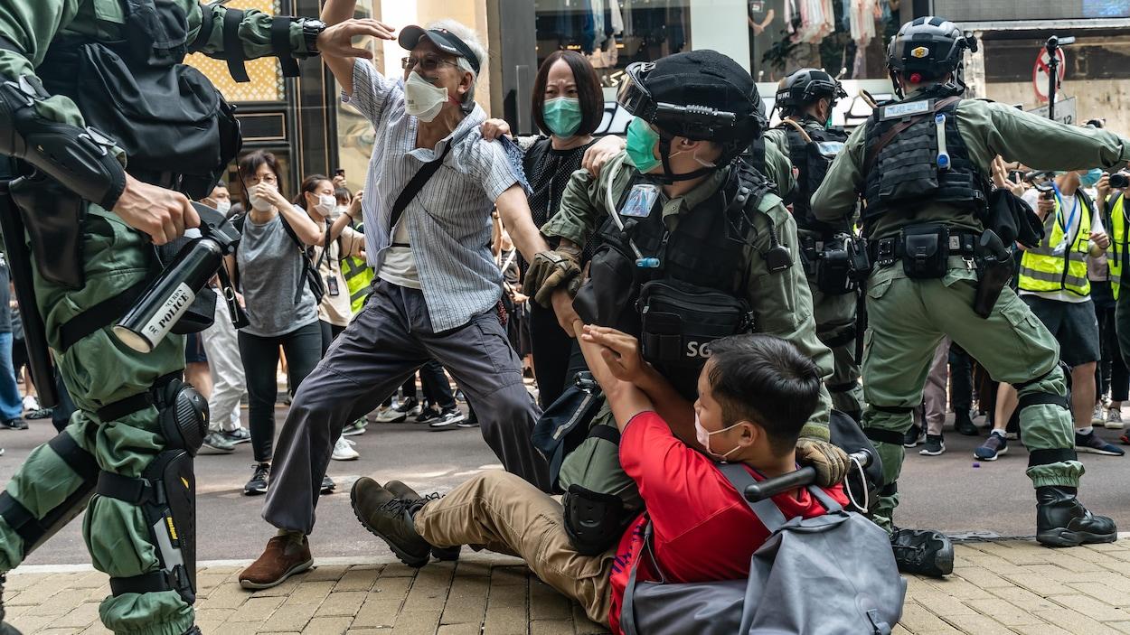 Des policiers repoussent un homme tandis qu'un agent immobilise un adolescent au sol.