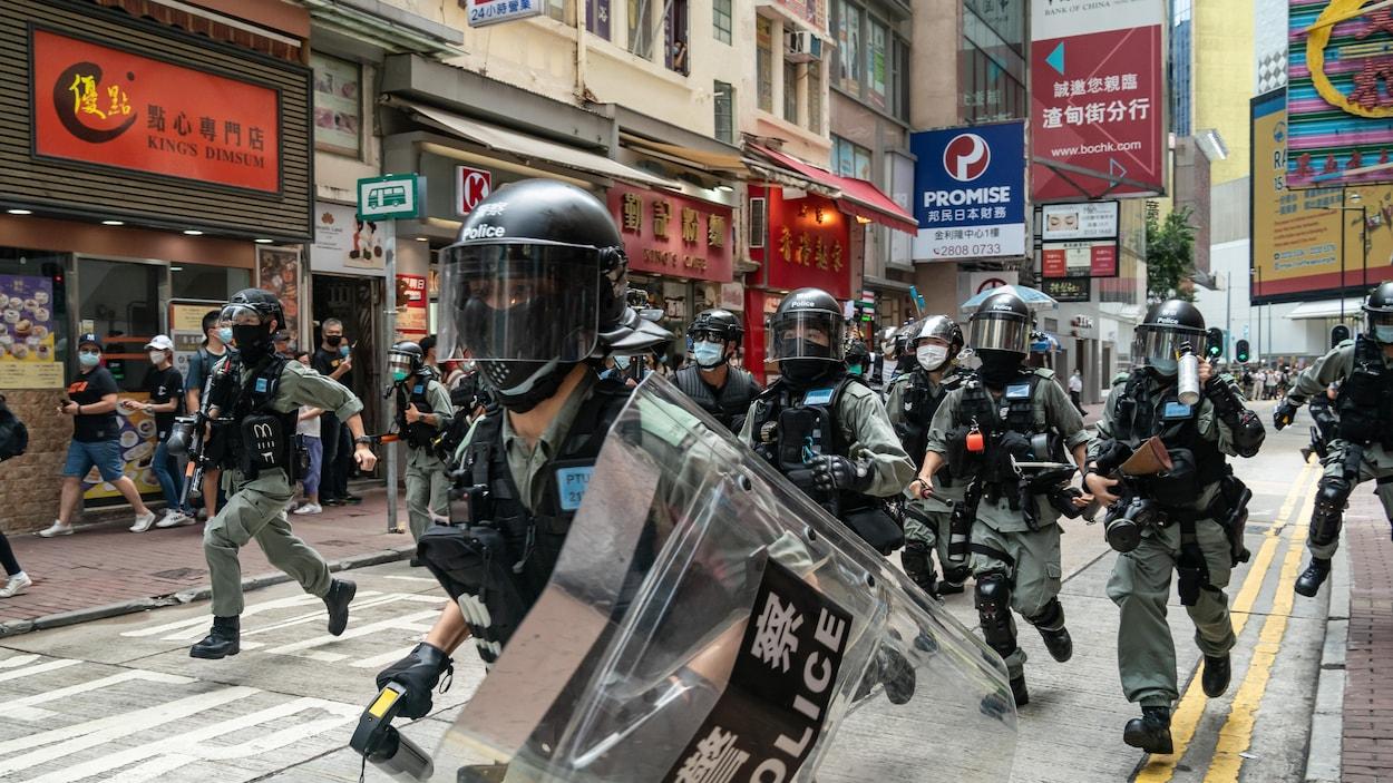 Les policiers courent au milieu de la rue, pendant que quelques piétons se serrent sur les devantures des magasins.