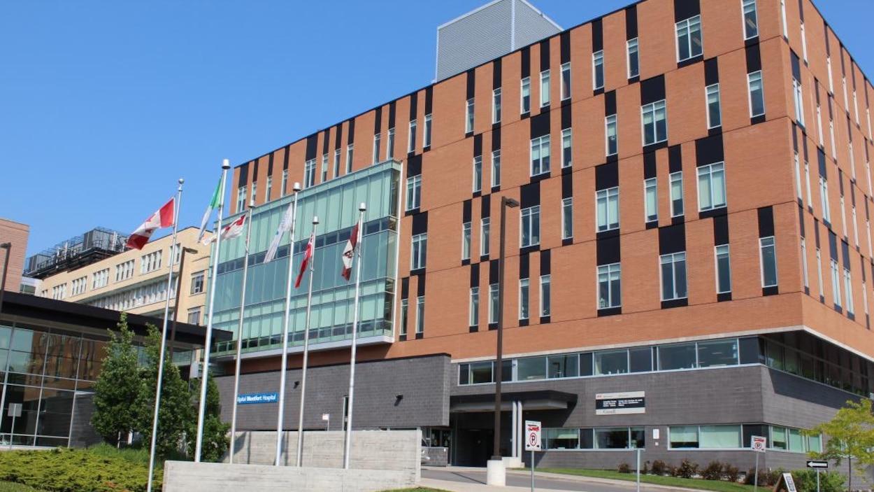 La façade de l'hôpital Montfort devant lequel se trouve des drapeaux.