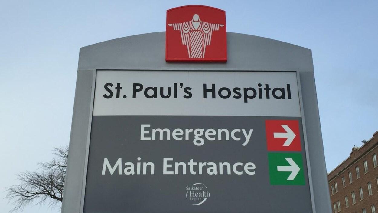 L'enseigne de l'Hôpital Saint-Paul et son bâtiment en briques rouges sous un ciel bleu