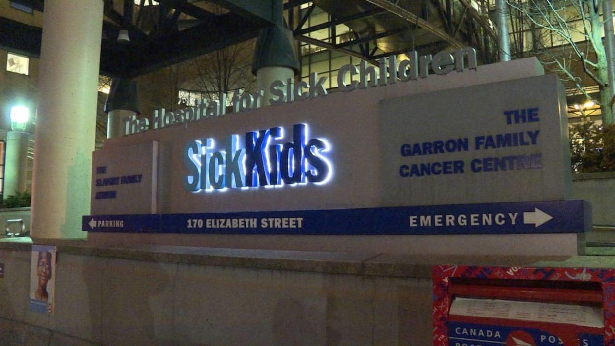 Enseigne lumineuse devant un bâtiment qui indique le nom de l'hôpital ainsi que différentes directions.