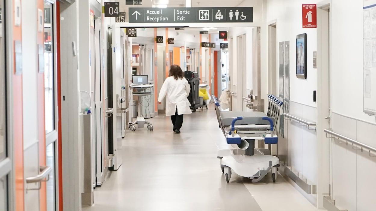 Un médecin marchant dans un corridor d'hôpital.