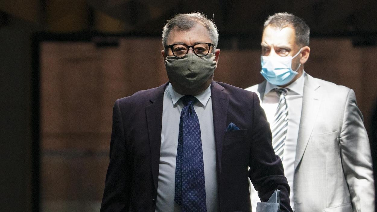 Le docteur Horacio Arruda debout et portant un masque. Derrière lui, un autre homme avec un couvre-visage.