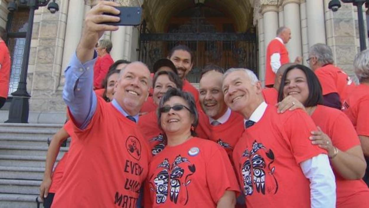 Le premier ministre de la Colombie-Britannique, John Horgan, entouré de membres de son Cabinet et de Phyllis Webstad, qui a proposé le port du chandail orange, lors de la prise d'un égoportrait sur les marches de l'assemblée législative à Victoria.