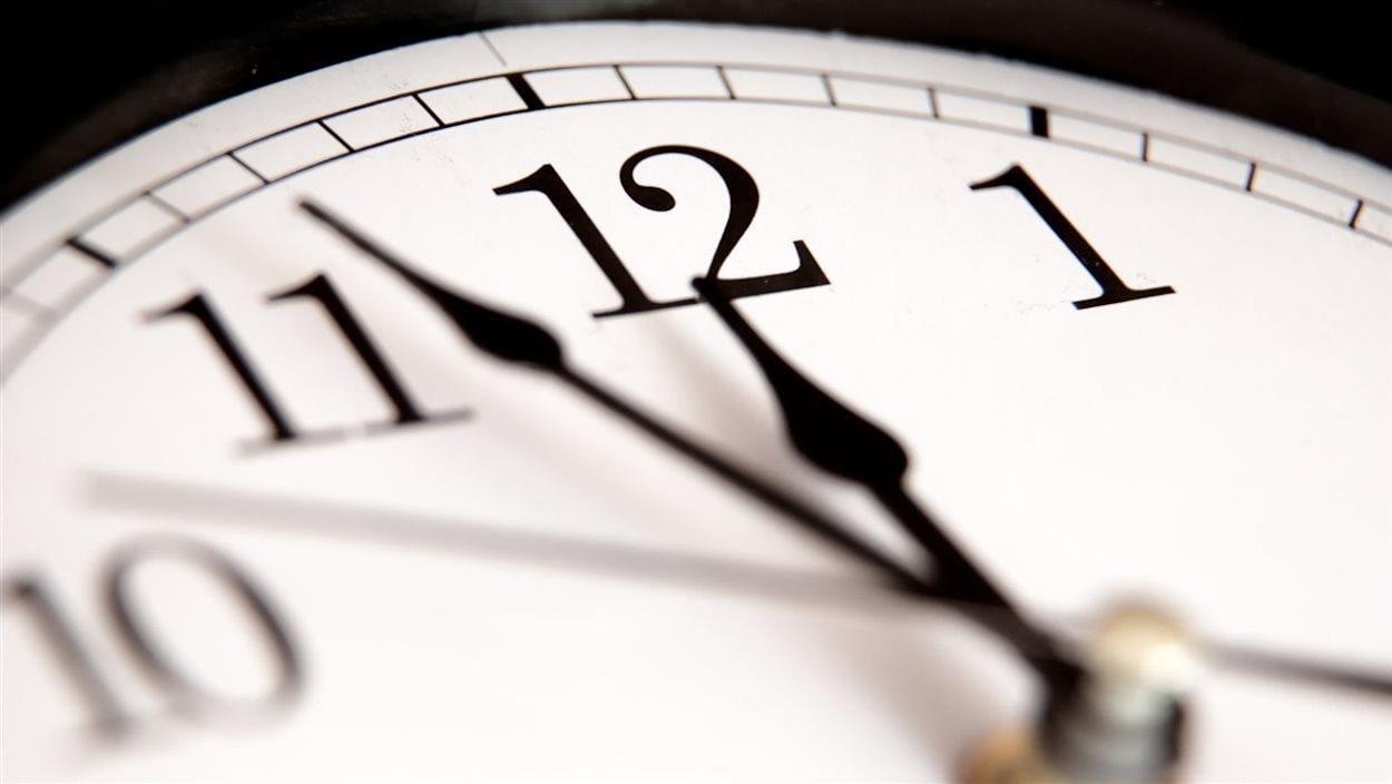Les aiguilles d'une horloge s'approchent de minuit.