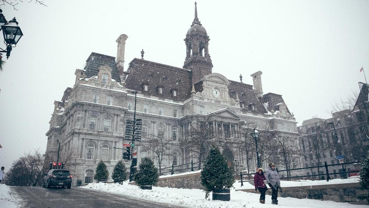 Des gens se baladent sur la place Jacques-Cartier devant l'hôtel de ville de Montréal, alors qu'une fine neige tombe dans le Vieux-Montréal.