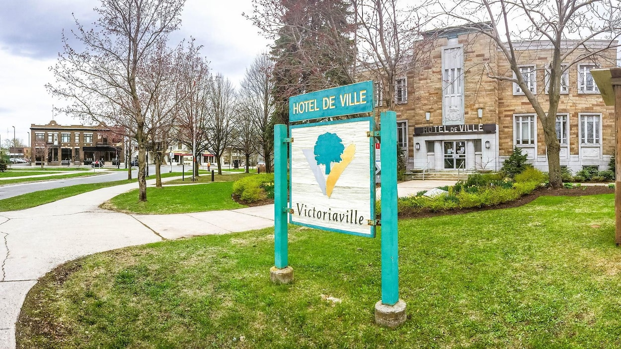 Extérieur de l'hôtel de ville sans feuille dans les arbres avec une affiche indiquant Victoriaville.