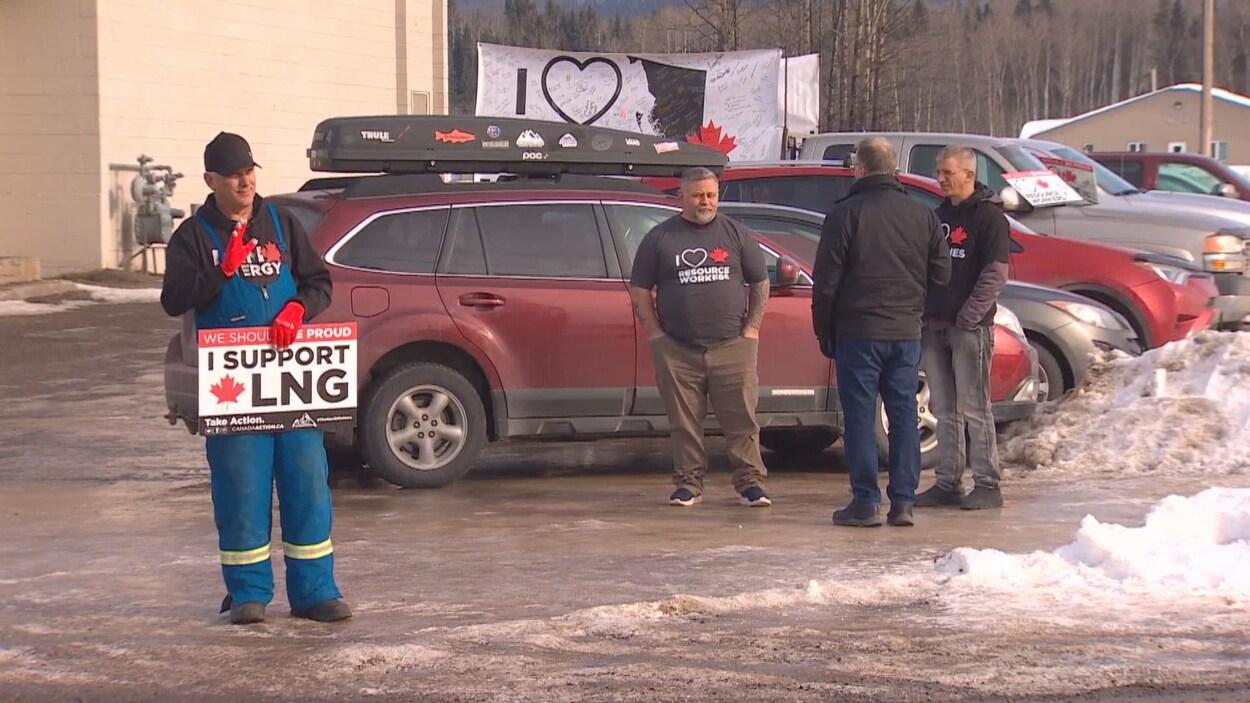 Quatre hommes debout dans un stationnement, dont un tient dans une main une affiche en soutien au gaz naturel liquéfié.