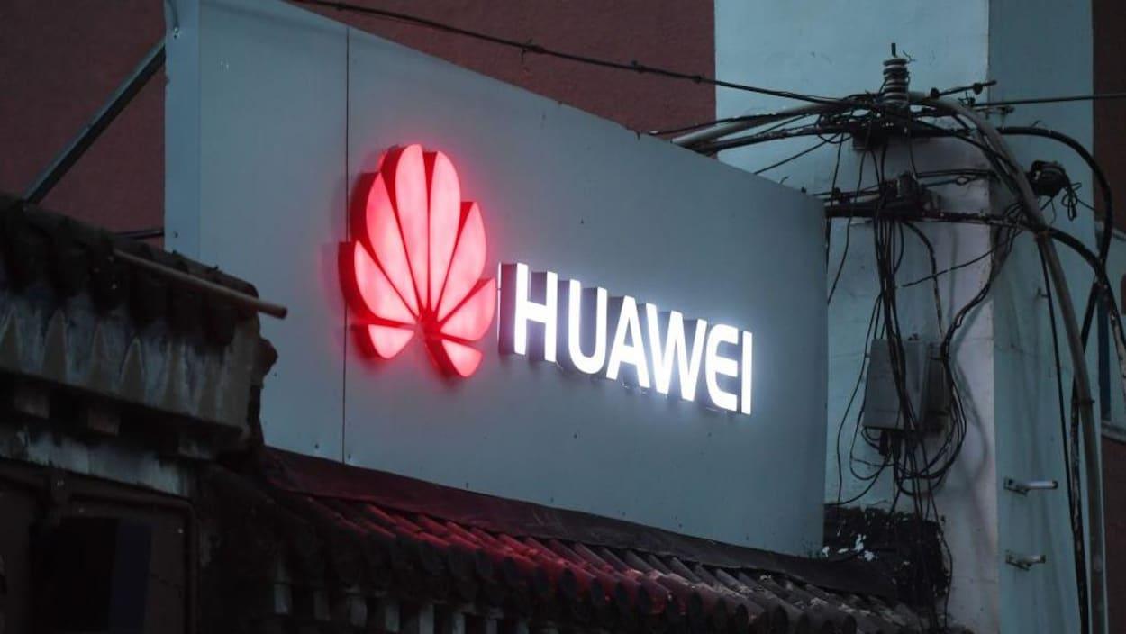 Une enseigne lumineuse porte le logo du fabricant chinois Huawei au-dessus d'un commerce qui vend des téléphones intelligents à Pékin, en Chine.