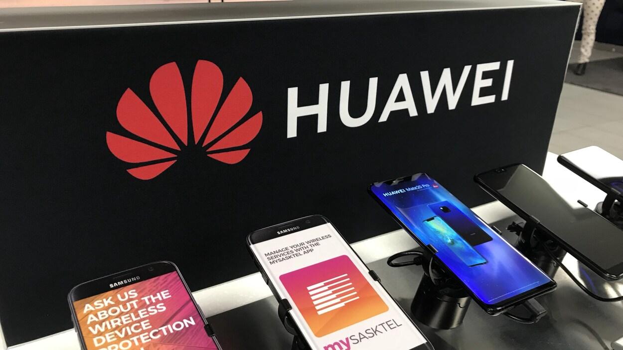 Des téléphones cellulaires vendus par SaskTel devant un présentoir portant le logo de Huawei.