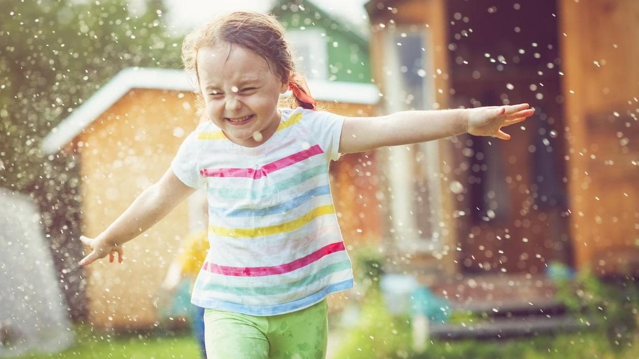 Une fillette court sous un jeu d'eau.