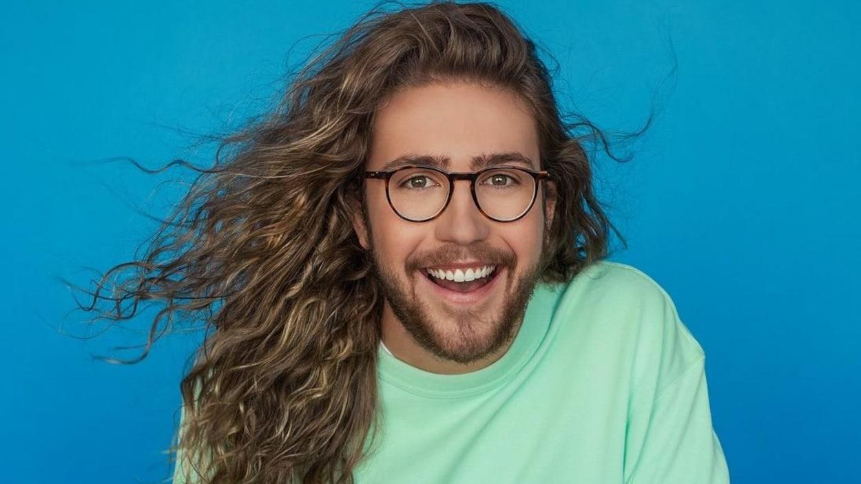 Le jeune homme porte des lunettes et pose devant un fond bleu.