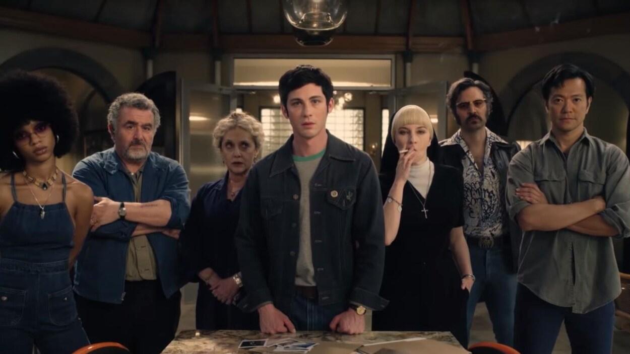 Sept personnes sont debout autour d'une table.