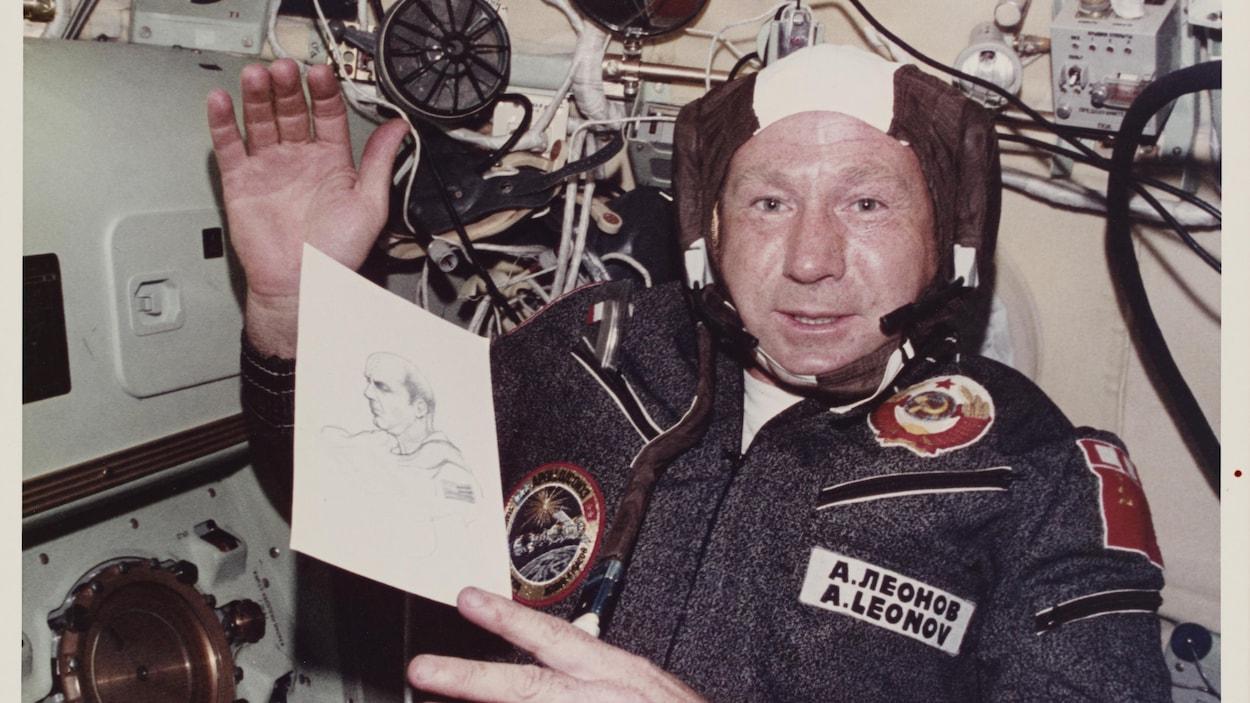 Alexei Leonov tient un portrait d'un collègue pendant une mission spatiale.