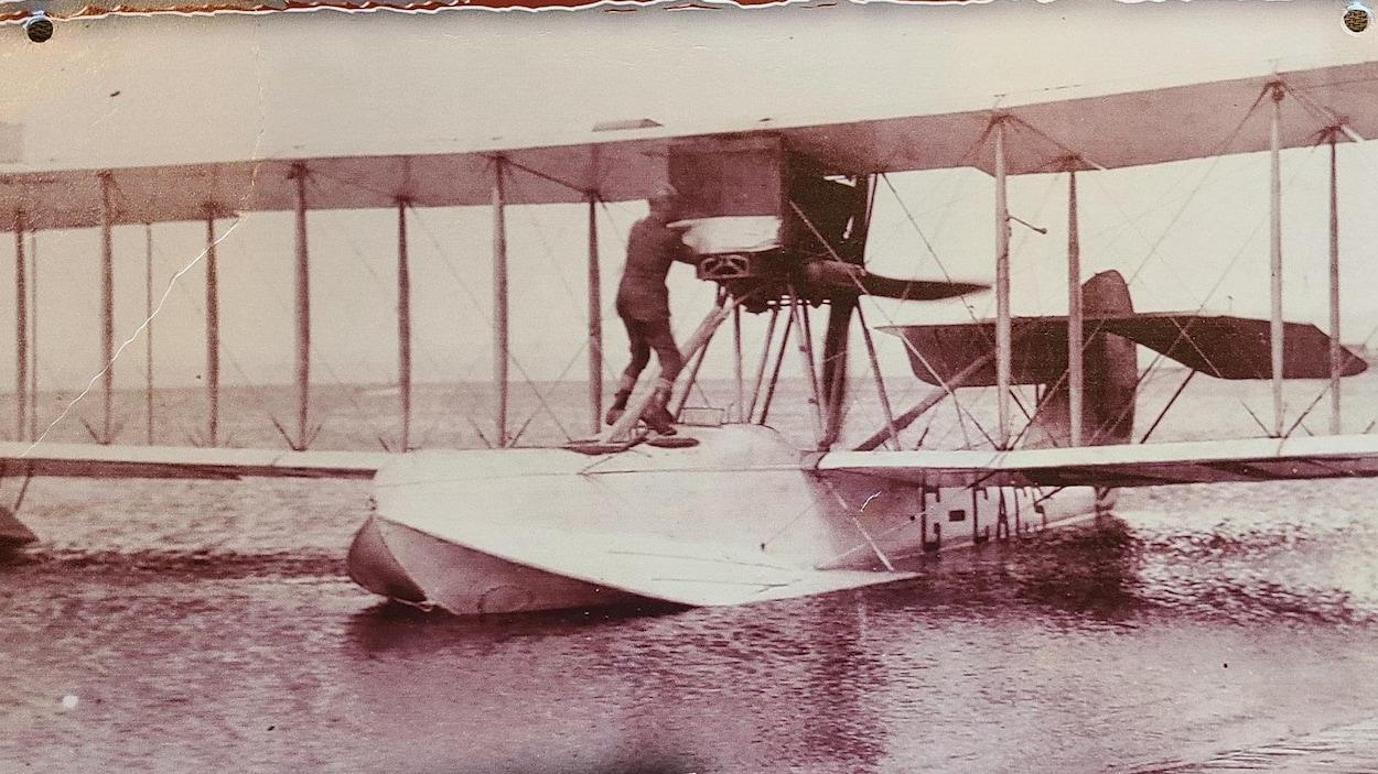 Une vieille photo en noir et blanc d'un hydravion sur un lac.