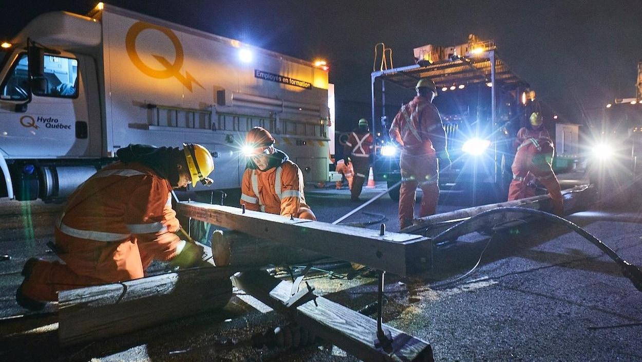 Des travailleurs d'Hydro-Québec s'affairent, dans leur uniforme de travail orange, à réparer un poteau tombé sous la force du vent. Ils travaillent à la noirceur, éclairés par des lampes frontales.