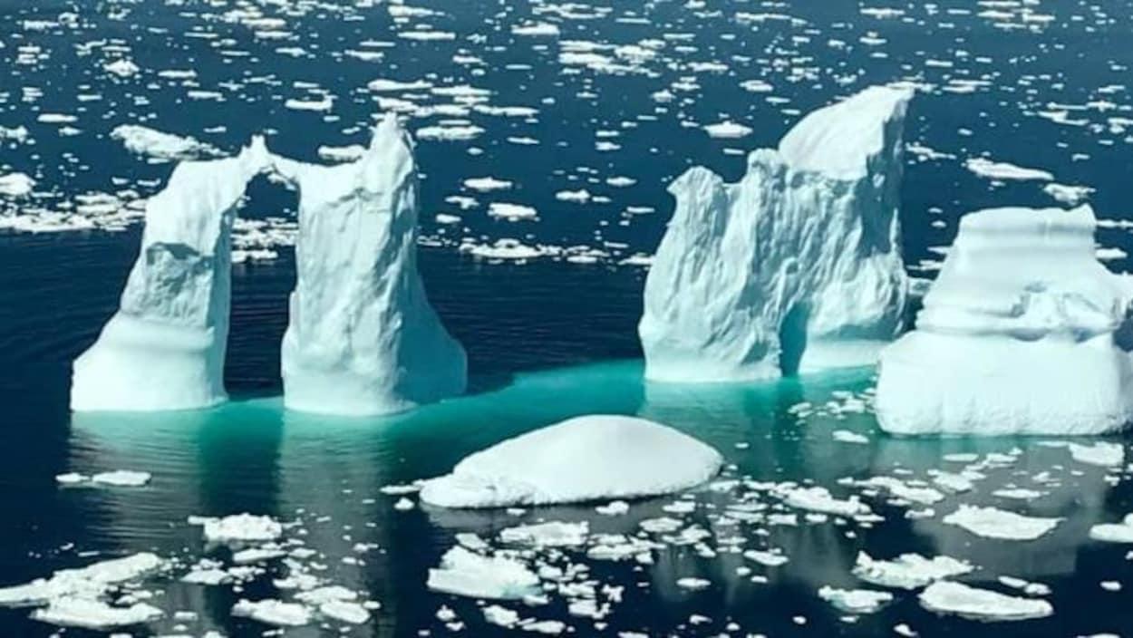 Un iceberg à quatre pointes dans la mer près de White Bay, avec de l'eau turquoise qui l'encercle.