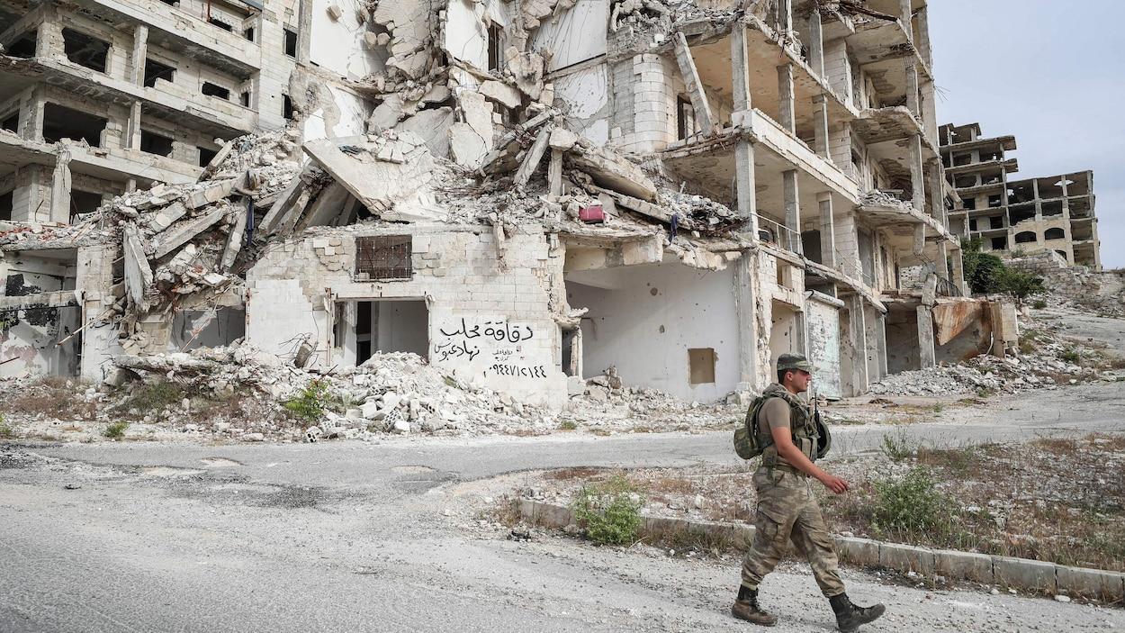 Un soldat marche devant un immeuble en ruines.