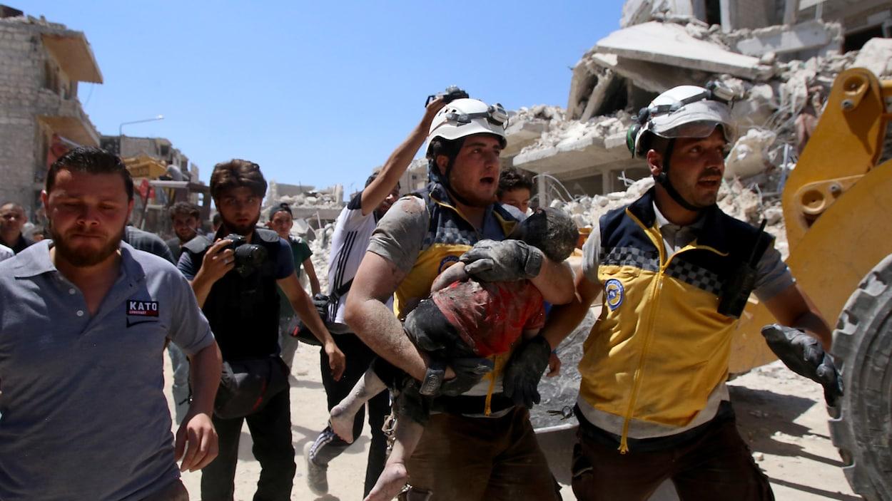 Un homme coiffé d'un casque blanc tient un enfant dans ses bras devant les décombres d'un immeuble.
