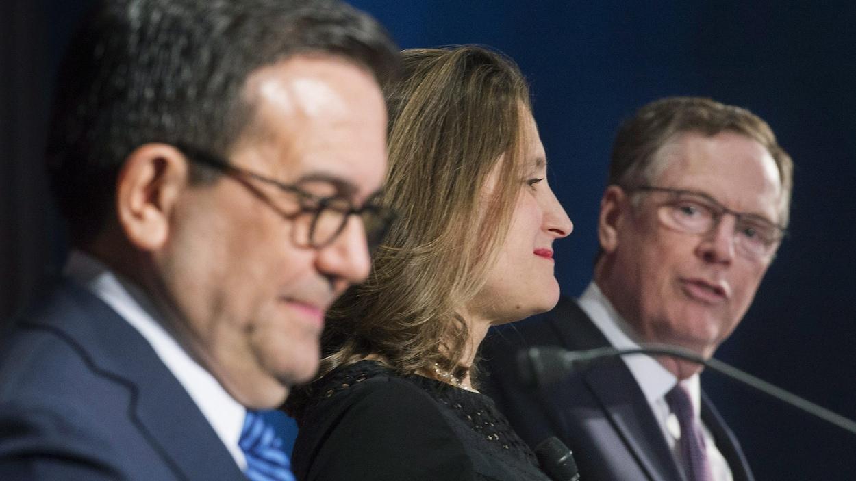 Plan rapproché des trois ministres vus de profil, M. Villarreal étant plus près et Mme Freeland au centre, tandis que M. Lighthizer, plus, loin, se tourne vers ses vis-à-vis.