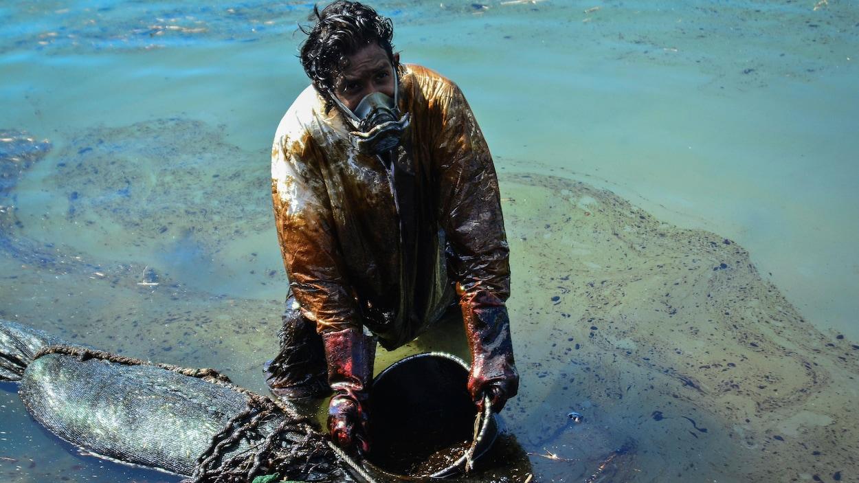 Un homme récupère du pétrole qui s'est déversé dans la mer à l'aide d'un genre de tamis.