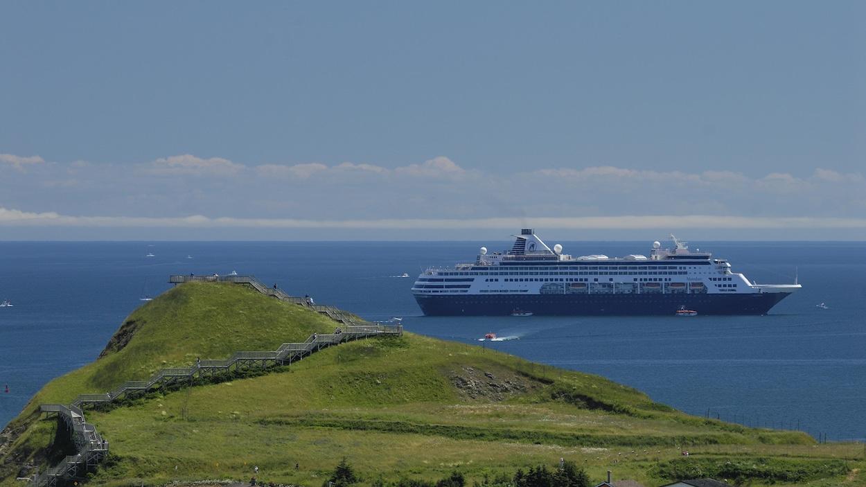 Un navire de croisières passe près de la Butte de Cap-aux-Meules, à l'entrée des Îles-de-la-Madeleine.