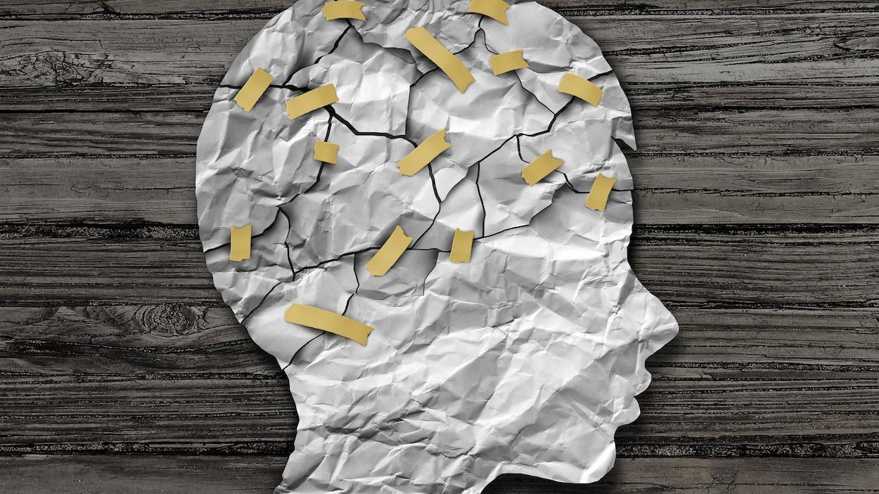 Une tête d'enfant illustrée en papier avec les éléments du cerveau reliés par des rubans gommés