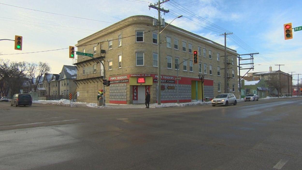 Un piéton marche devant l'immeuble de trois étages de la rue Ellice qui a pris feu