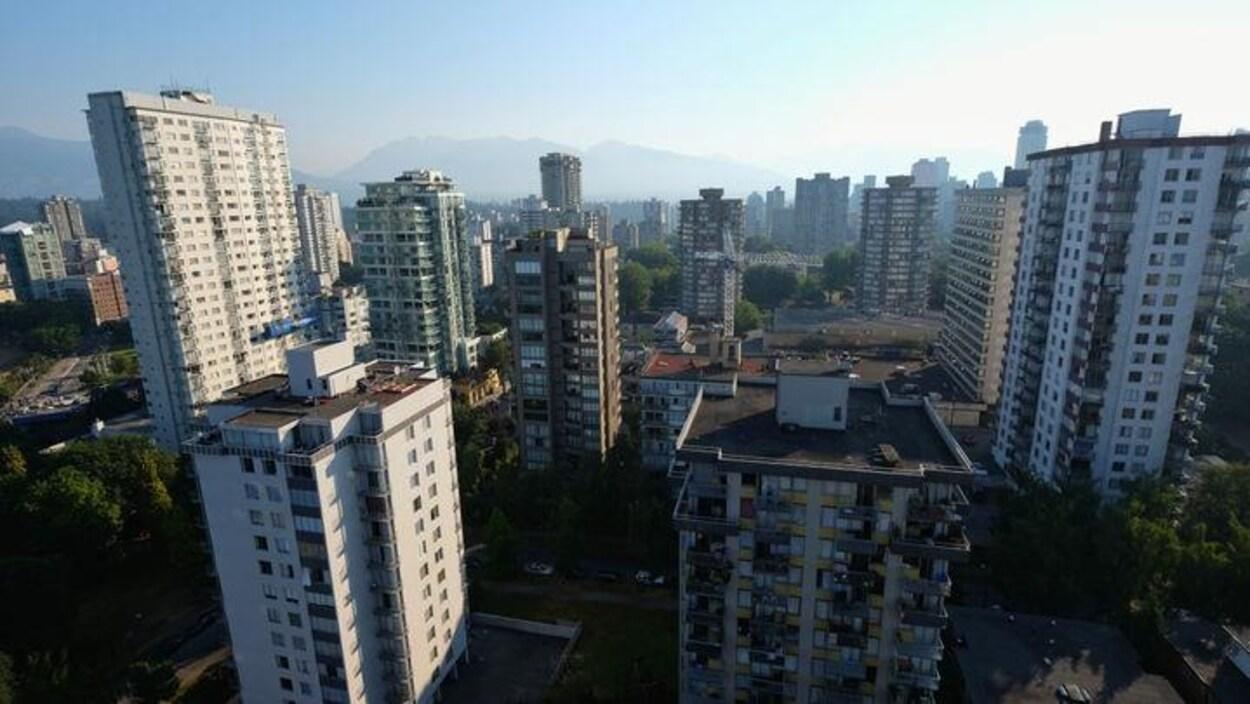Point de vue de la ville de Vancouver depuis la fenêtre d'une tour à logements. On y voit plusieurs tours avec les montagnes en arrière plan.