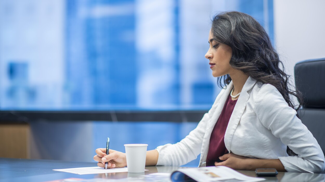 Une femme prend des notes dans un bureau.