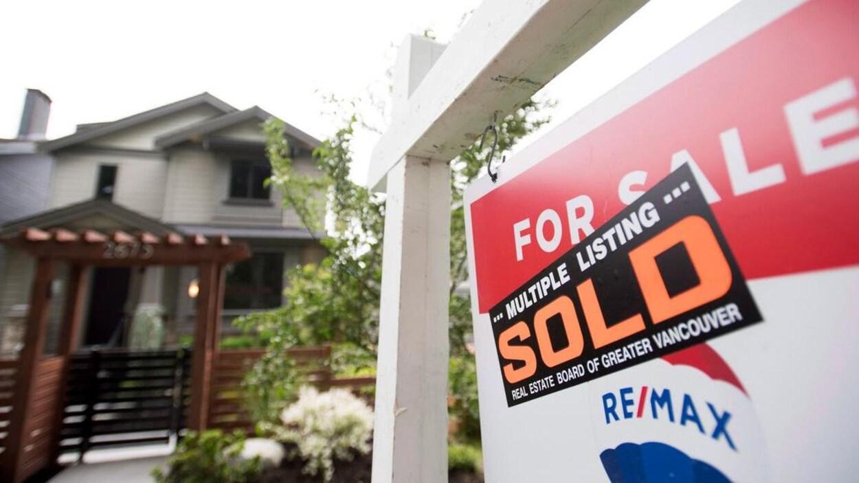 Une maison à l'arrière-plan, une pancarte affichant une maison vendue à l'avant-plan