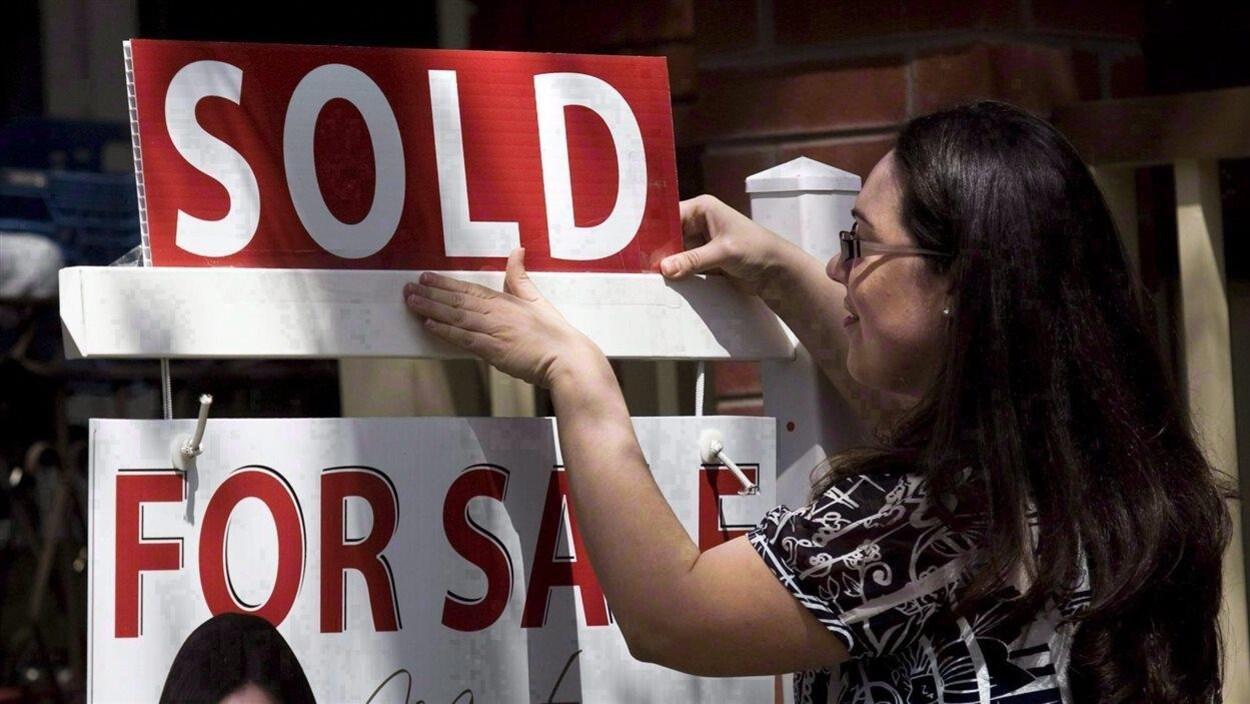 Une femme ajoute la mention « vendu» au-dessus d'un panneau « à vendre ».
