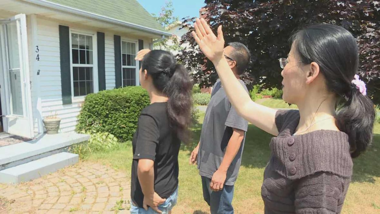 Une agente immobilière et deux acheteurs devant une maison.