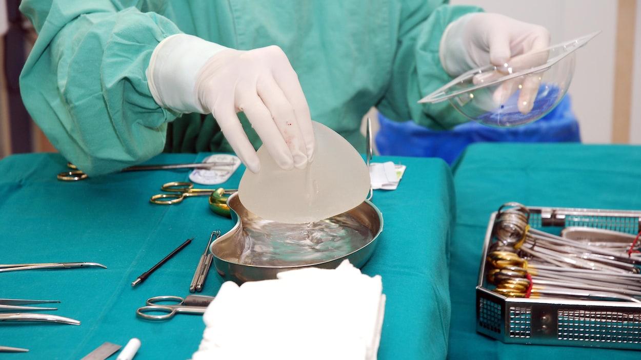 Une infirmière tient dans sa main un implant mammaire.