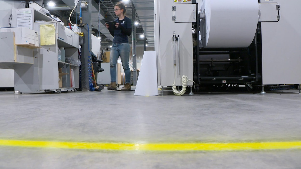 Une ligne au sol et une employée qui travaille derrière.